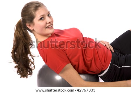 A woman laying on a ball with a smile on her face. - stock photo