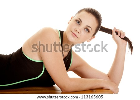 A woman laying on a bench in her black and green workout top with a serious expression on her face holding on to her pony tail - stock photo