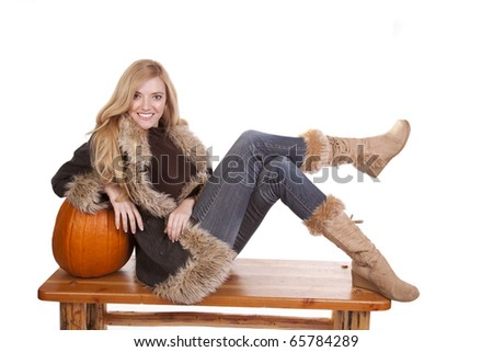 a woman laying on a pumpkin in her warm fuzzy boots and coat. - stock photo