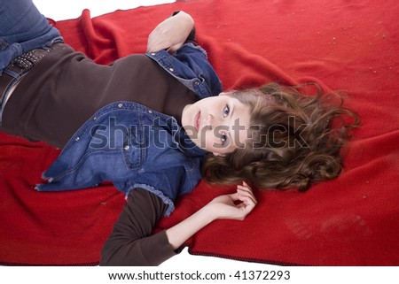 a woman laying on a red blanket with hands in her hair with a sexy look on her face. - stock photo