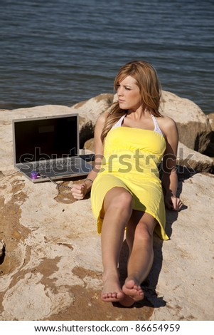 A woman laying on a rock in the outdoors trying to get some sun with a serious expression on her face still locked to her computer. - stock photo