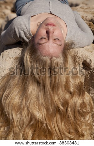 A woman laying on a rock with her hair flowing down the rock with her eyes closed. - stock photo