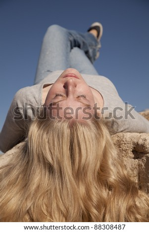 A woman laying on a rock with her hair flowing with her eyes closed. - stock photo