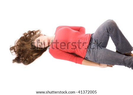 A woman laying on her back with her hair fanned out with a red shirt on and denim pants with a serious look on her face. - stock photo