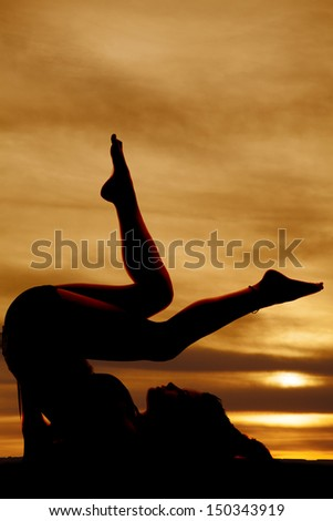 A woman laying on her back with her legs up barefoot in the sunset silhouetted. - stock photo