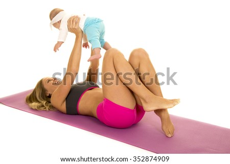 A woman laying on her fitness mat with her baby high in the air - stock photo