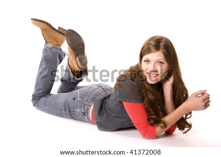 A woman laying on her stomach with her hands in her hair, cowboy boots up in the air with a small smile on her face. - stock photo