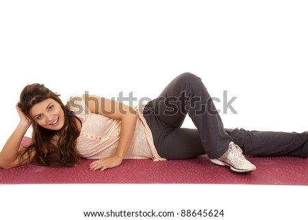 A woman laying on her yoga mat stretching with a smile on her face. - stock photo