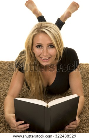 a woman laying on the carpet reading her book relaxing. - stock photo