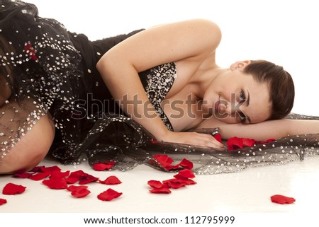 A woman laying on the ground on her formal dress with red rose petals all around her. - stock photo