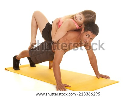A woman laying on top of a man while he is doing a push up. - stock photo
