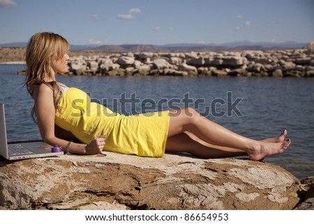 A woman laying out on vacation trying to get some sun, but still can not get away from her computer, she is locked and chained to work. - stock photo