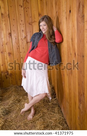 A woman leaning against a wood wall with a white skirt on and her bare ankles crossed with a smile on her face. - stock photo