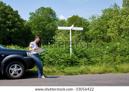 A woman leaning on her car as she reads a map next to a roadside sign, the sign is blank for you to add your own text. - stock photo