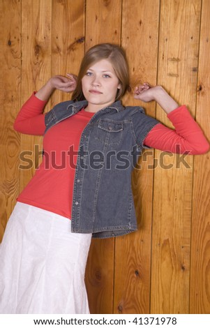 A woman leaning up against a wood wall with arms up and a sexy look on her face. - stock photo