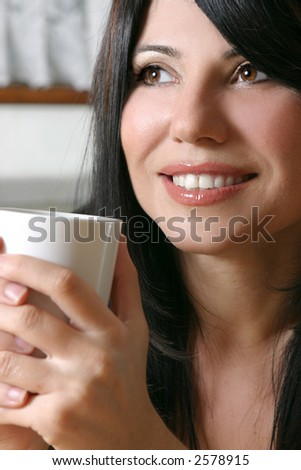 A woman leisurely relaxes with a hot beverage. - stock photo