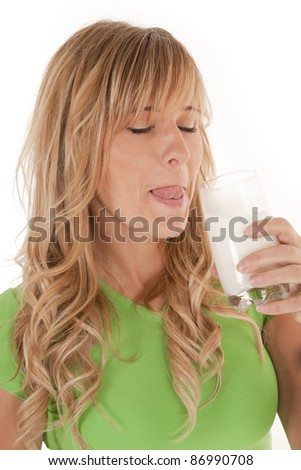 a woman licking her lips after having a drink of milk. - stock photo
