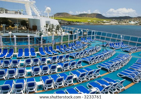 A woman lies alone on the deck of a cruise ship - stock photo