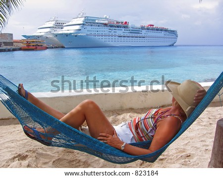 A woman lies in a hammock on a sandy beach and looks over at cruise ships in the port - stock photo