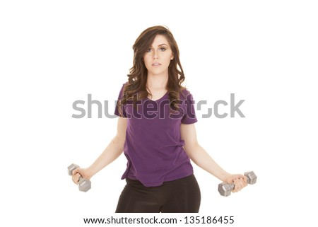 A woman lifting her weights with a serious expression on her face