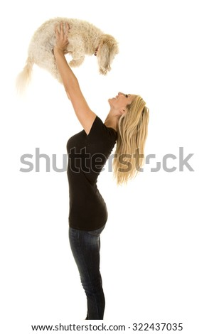 a woman lifting up her Maltese dog up over her head with a smile. - stock photo