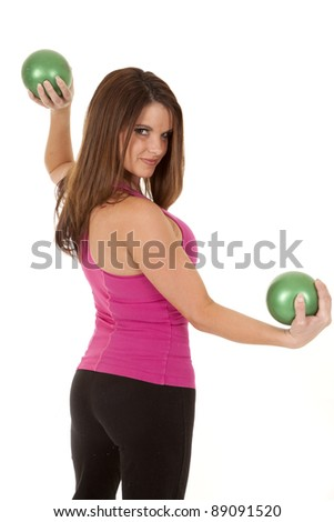 A woman lifting weighted green balls with a smile on her face.