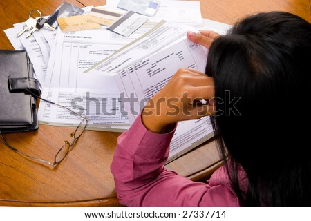 A woman looked so stress looking at credit card's bill all other debt invoice.