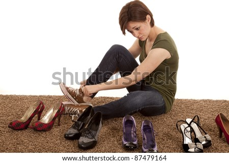 a woman looking at all the new shoes while she is touching her old ones. - stock photo