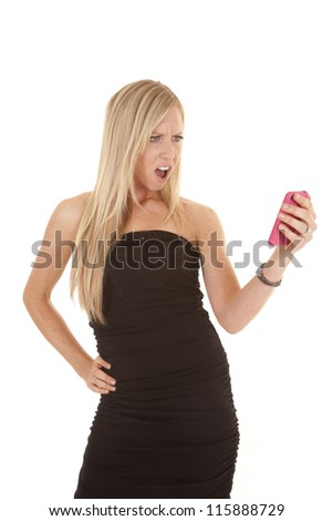 A woman looking at her cell phone with an upset expression on her face. - stock photo