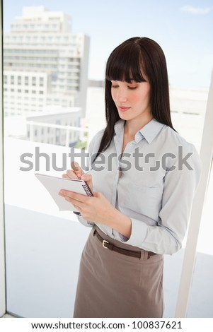 A woman looking at her note pad as she writes on it - stock photo