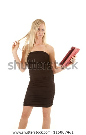a woman looking at her pad playing with her hair thinking. - stock photo