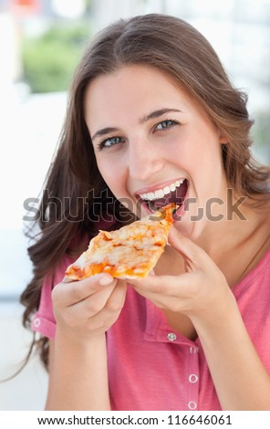 A woman looking at the camera in front of her as she is about to eat her pizza