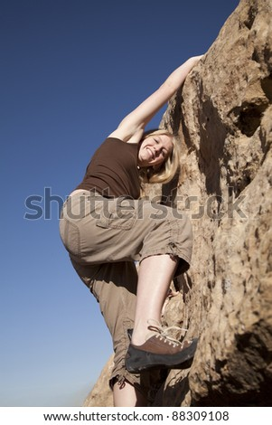 A woman looking at the camera while she is rock climbing. - stock photo