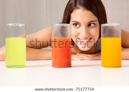 A woman looking at three science beakers filled with colored liquid - stock photo