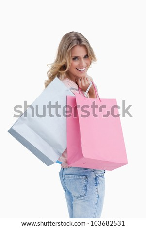 A woman looking back at the camera is carrying shopping bags over her shoulder against a white background - stock photo
