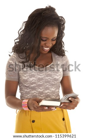 A woman looking down at her book laughing. - stock photo
