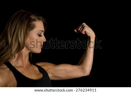 A woman looking down at her flexed muscle.