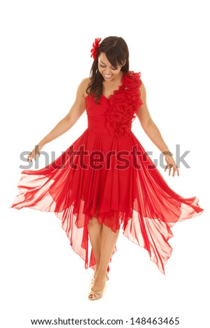 a woman looking down at her flowing red dress while she is laughing - stock photo