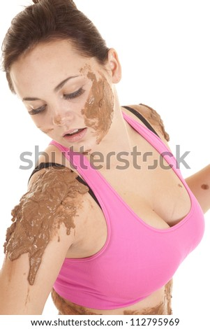 A woman looking down at the mud that is going down her shoulders. - stock photo