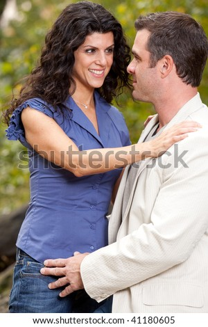 A woman looking happy at her husband / boyfriend - Shallow depth of field, focus on man - stock photo