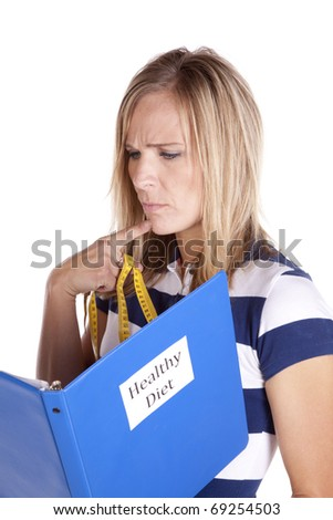 A woman looking in a book trying to eat healthy. - stock photo
