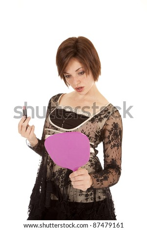 A woman looking in the mirror holding her lipstick. - stock photo