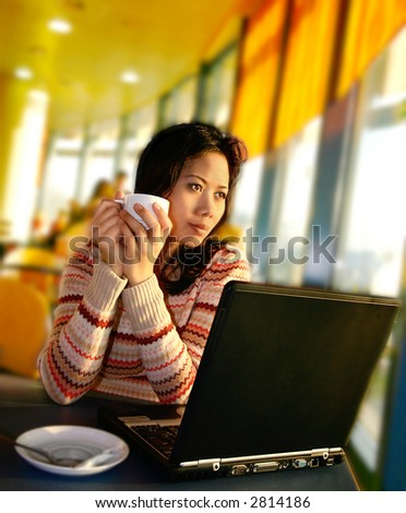 A woman looking out onto the airport runaway as she relaxes with a cup of coffee and catching up on some work.