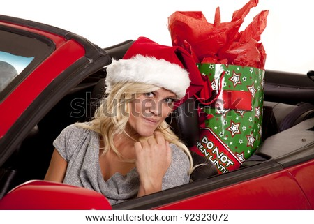 A woman looking out while she is wearing her Santa hat with a present in her back seat.