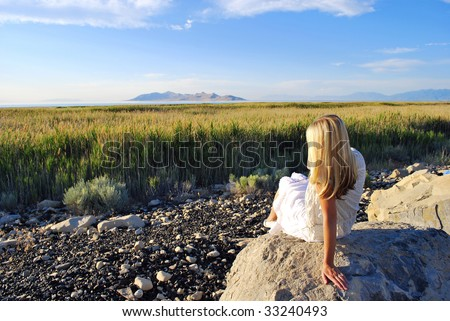 A woman looking over a field of grass. - stock photo