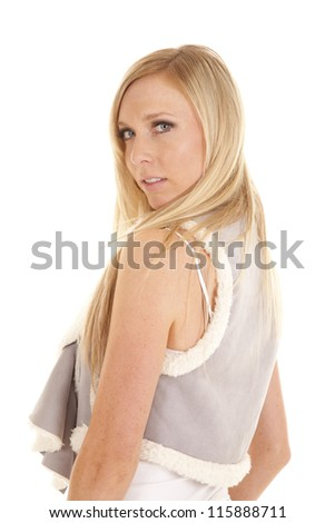 A woman looking over her shoulder in her gray vest with a serious expression on her face. - stock photo
