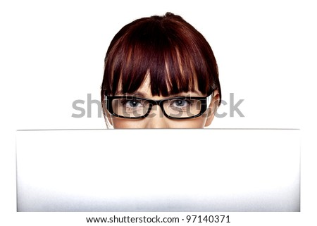A woman looking over the top of a laptop computer at you. Looking at technology. - stock photo