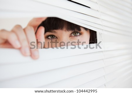 A woman looking through a closed set of blinds by opening them with her fingers - stock photo