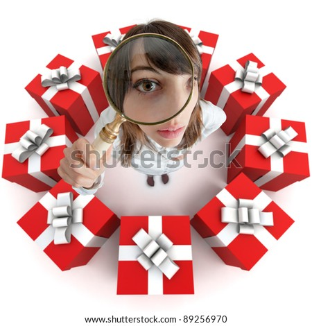 A woman looking through a magnifying lens surrounded by presents - stock photo