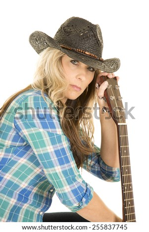 A woman looking to the side in her western wear with a serious expression on her face holding on to her guitar. - stock photo